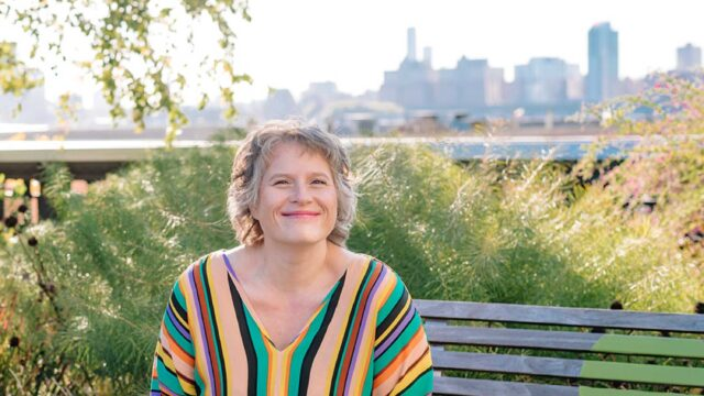 quick start guide to investing for self employed creatives | eowyn levene money coach | picture of woman seated and smiling non a bench in a colorful striped dress with green plants around her and city scape in background